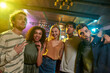 Portrait of young men and women looking at camera and smiling. Multiracial group of friends hanging out at party in the bar