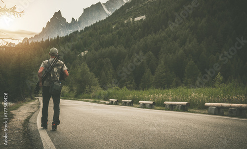 Foto Photographer with Camera and Tripod Walking Along Mountain Road