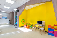 The Waiting Area With The Play Space For Children. Bright Yellow Play Space With Little Children's  Colorful Furniture And  Toys