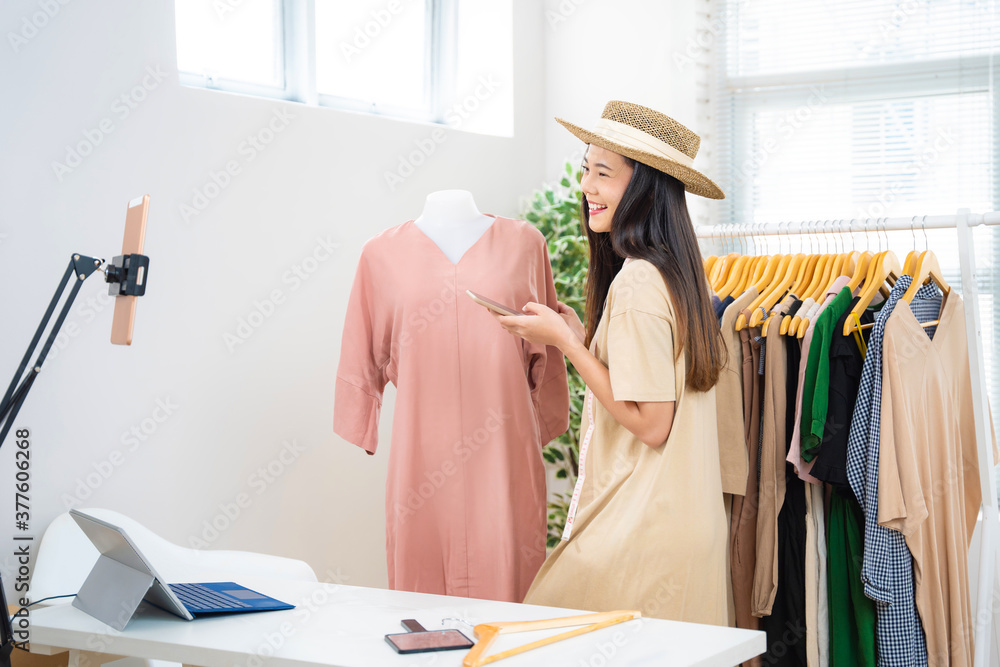 Fototapeta Asian woman selling vintage clothes, she is live on social media.