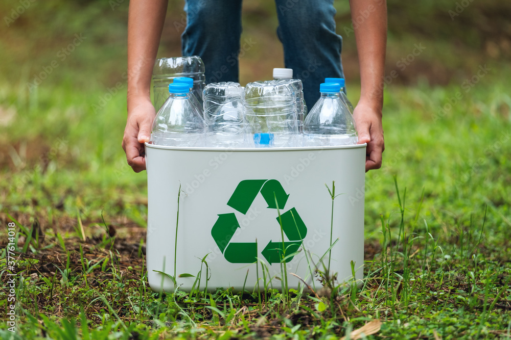 Fototapeta A woman holding a recycle bin with plastic bottles in the outdoors