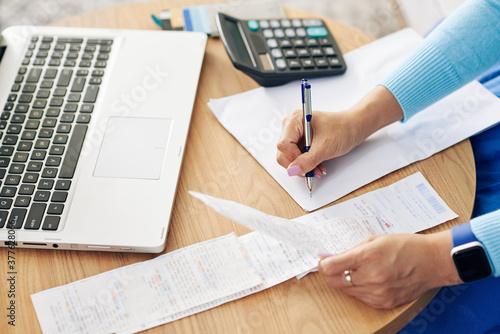 Fototapeta premium Close-up wizerunek kobiet przedsiębiorcy sprawdzania rachunków i pisania danych liczbowych na pustym arkuszu