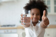 Leinwandbild Motiv Focus on happy small african american girls hands holding glass with fresh pure water and showing thumbs up gesture. Smiling little biracial kid recommending healthcare habit, morning refreshment.