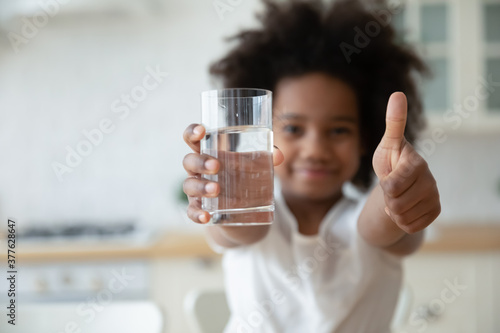 Focus on happy small african american girls hands holding glass with fresh pure water and showing thumbs up gesture. Smiling little biracial kid recommending healthcare habit, morning refreshment.