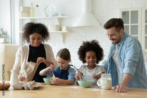 Fotografie, Obraz Happy multiracial young couple involved in cooking pastry with adorable mixed race daughters in modern kitchen