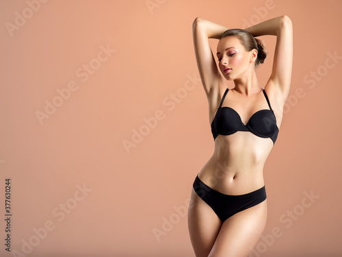 Obraz Young girl in black underwear with an ideal body, posing in the studio. - fototapety do salonu