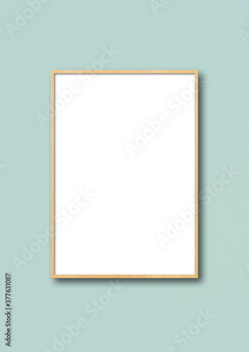 Fototapeta Wooden picture frame hanging on a light blue wall obraz