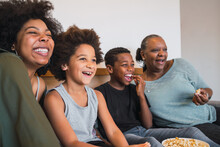 Grandmother, Mother And Children Watching A Movie At Home.