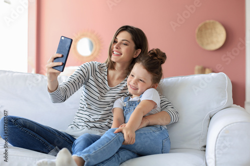 Fotomural Beautiful young mother and her little daughter taking a selfie with a smartphone at home on the couch