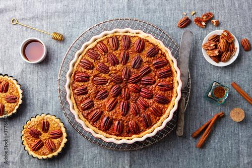 Tablou Canvas Pecan nut pie, tart in baking dish. Grey background. Top view.