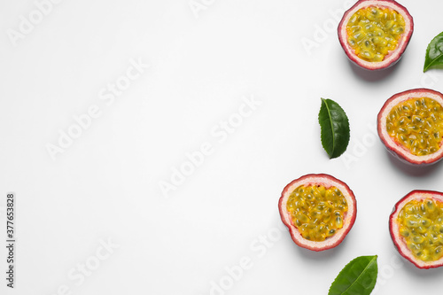 Fotografie, Obraz Halves of passion fruits (maracuyas) and green leaves on white background, flat lay