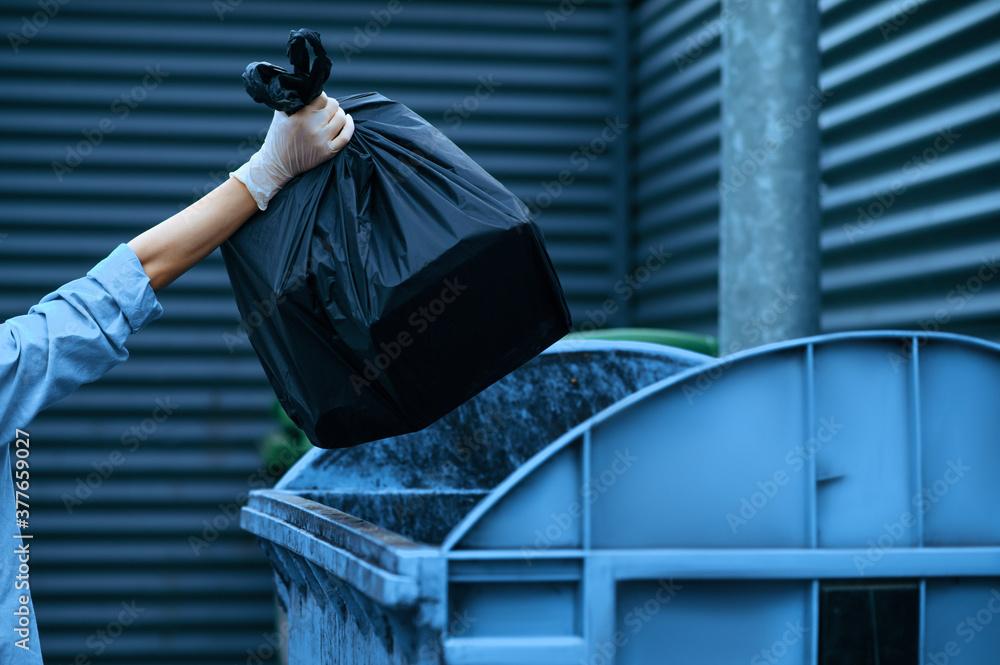 Fototapeta Volunteer puts plastic trash bag into the bin