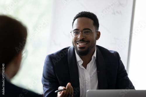 Smiling African American young businessman in glasses talk with business partner at office meeting. Happy motivated biracial man boss or CEO have talk, discuss cooperation with colleague at briefing.