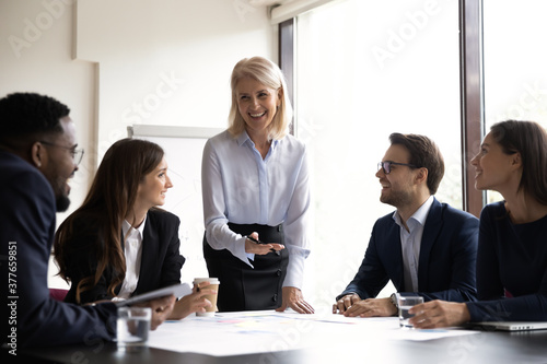Smiling middle-aged businesswoman hold lead meeting with diverse colleagues discuss ideas together. Happy multiracial businesspeople have fun brainstorming at team office briefing. Teamwork concept.