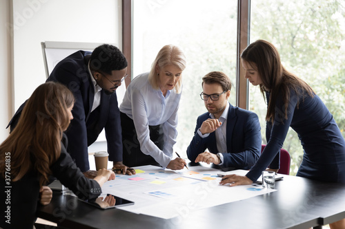 Focused multiracial businesspeople brainstorm analyze company financial documents at meeting together. Concentrated diverse colleagues talk discuss business project paperwork at briefing in office. - 377661835