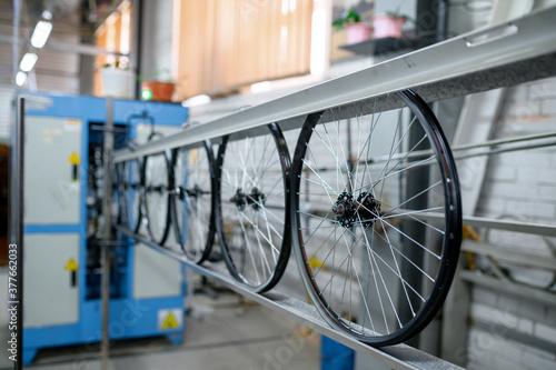 Fototapeta New aluminum bicycle wheels on assembly line obraz