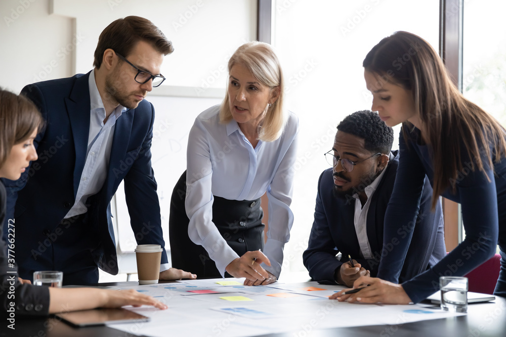 Fototapeta Concentrated diverse businesspeople talk brainstorm at team meeting discussing paperwork together. Focused multiracial colleagues analyze financial documents at briefing in office. Teamwork concept.