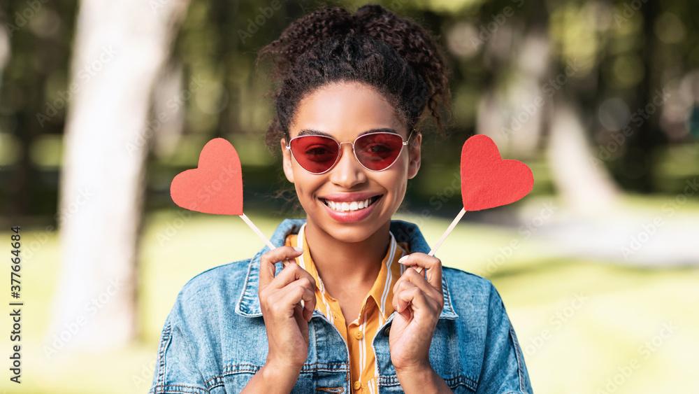 Fototapeta Black Girl Holding Two Paper Hearts Posing Standing In Park