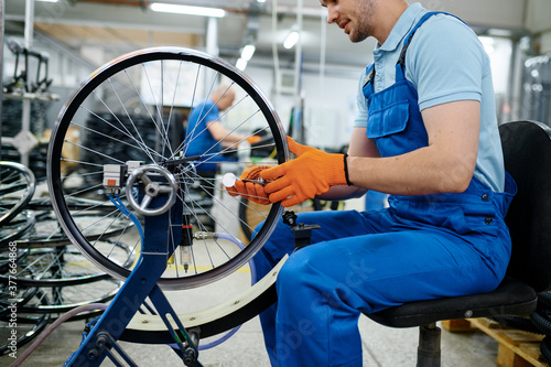 Male worker at the machine tool checks bicycle rim