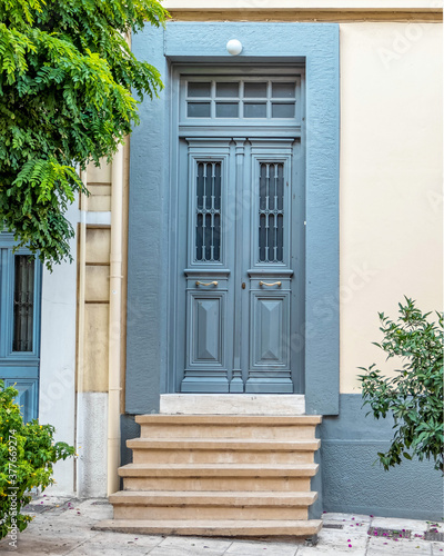 A vintage house front door and plant by the sidewalk, Athens, Greece