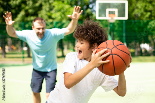 Fototapeta Excited dad playing basketball with his son outdoors obraz