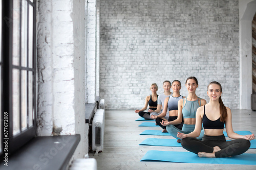 Group of women in the gym practice yoga, lotus position. Canvas