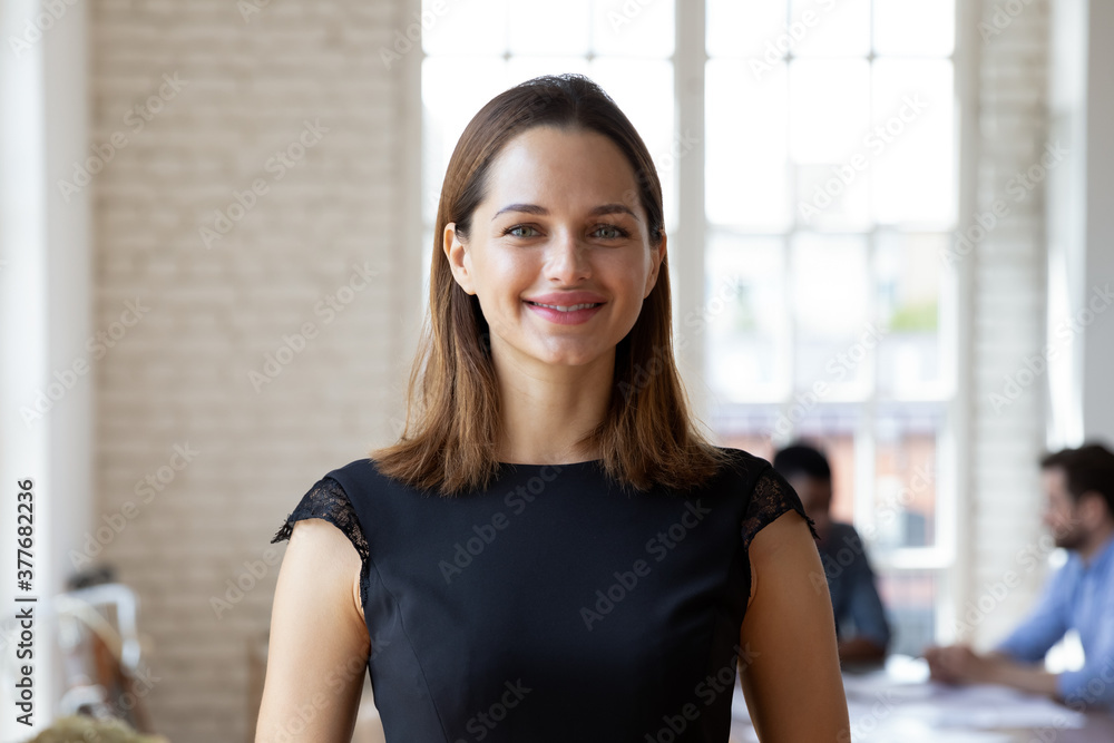 Fototapeta Headshot portrait of smiling millennial businesswoman stand forefront in office look at camera posing, happy confident young Caucasian female employee or company boss CEO show confidence in boardroom