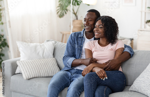 Obraz na plátně Happy black lovers watching movie together at home