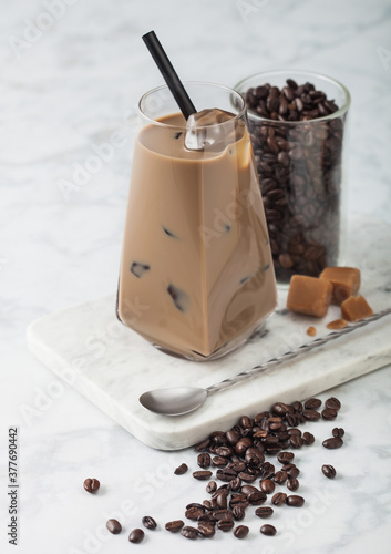 Valokuvatapetti Modern glass of iced coffee with milk on marble board with jar of coffee beans and salted caramel and long spoon on light background