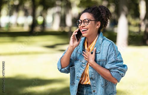 Obraz Happy African American Girl Talking On Cellphone Walking In Park - fototapety do salonu
