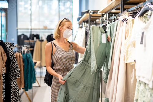 Fototapeta Fashionable woman wearing protective face mask shopping clothes in reopen retail shopping store. New normal lifestyle during corona virus pandemic. obraz