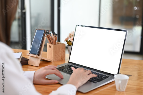 Cropped shot woman typing mockup laptop computer with blank screen..