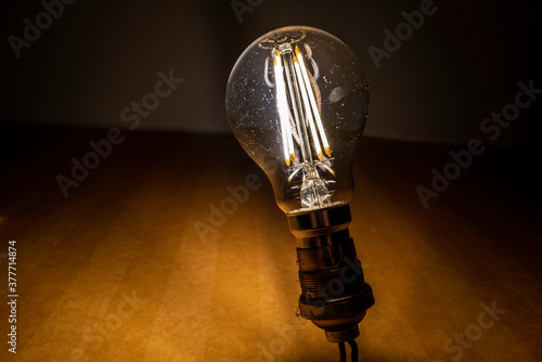 Obraz ampoule LED allumée sur douille B22 - fototapety do salonu