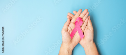 Tablou Canvas October Breast Cancer Awareness month, adult Woman  hand holding Pink Ribbon on blue background for supporting people living and illness