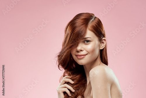 Pretty woman with long beautiful hair grooming hairstyle glamor naked shoulders pink background