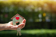 Investor Hand Holding The Home With Red Heart And House Key In The Public Park, Saving For Buy Real Estate For Business Investment Concept.