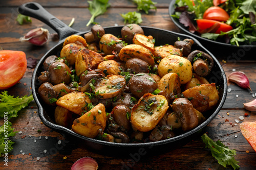 Fototapeta Baked potato with mushrooms and herbs in iron cast pan on wooden table