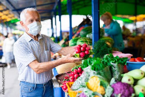Fototapeta retired european man wearing medical mask protecting against the virus buying radishes and cabbage in market obraz