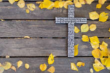 Autumn Background. White Wooden Cross With The Lord's Prayer On A Shabby Dark Wooden Board With Yellow Leaves