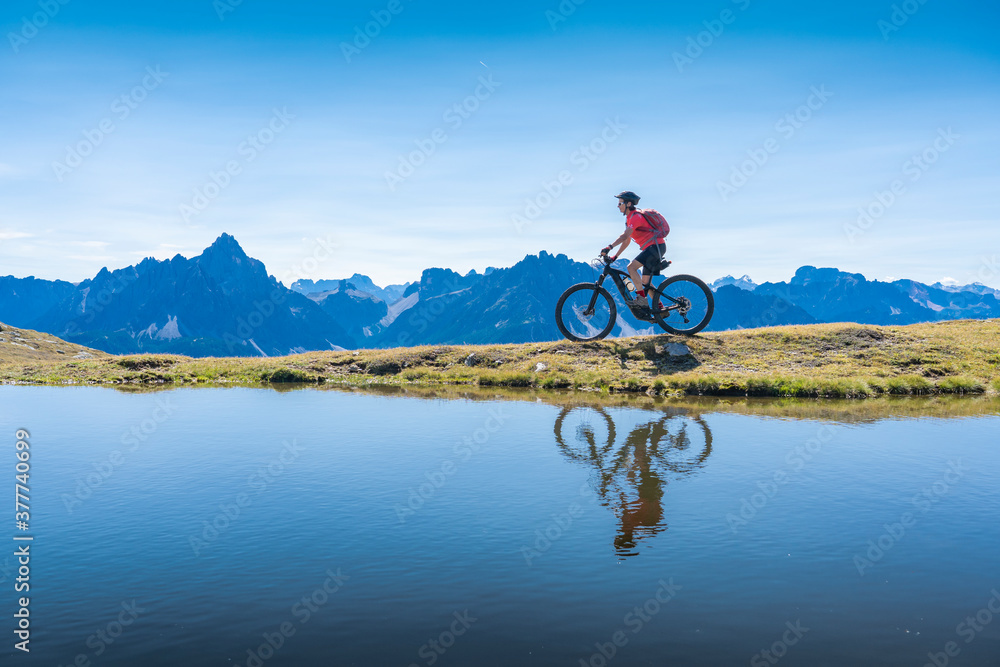 Fototapeta nice woman riding her electric mountain bike the Three Peaks Dolomites, reflecting herself in the blue water of a cold mountain lake