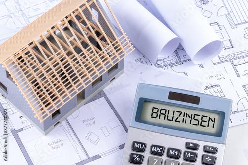 Cuadros en Lienzo Taschenrechner mit dem Schlagwort Bauzinsen und einer Rohbau Immobilie mit Baupl