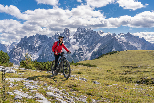 nice and active senior woman riding her electric mountain bike on the high plateau of Pratto Piazzo in the three peaks Dolomites , rocky silhouette of Mount Cristallo in background, South Tirol, Italy #377742039