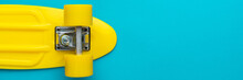 Minimalist Flat Lay Photo Of Yellow Plastic Mini Cruiser Board On Blue Background. Top View Of Bright Yellow Cruiser Skateboard With Copy Space.