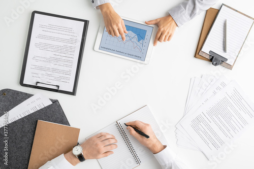 Flat layout of hands of two young managers or brokers analyzing online graphs