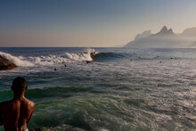 Man Watching Surfers Surfing At Sunrise In Rio De Janeiro, Brazil. Urban Buildings Under The Sun Far Away And Nice Ocean View. Travel Destination Holiday Vacation New Normal Reopening Concept.