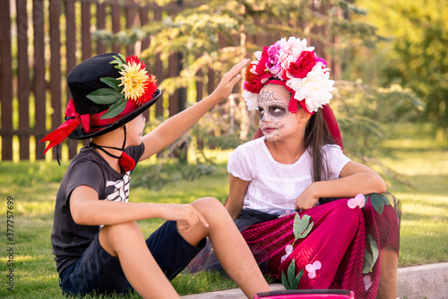 Cute boy in hat and t-shirt touching floral wreath on head of pretty girl #377757699
