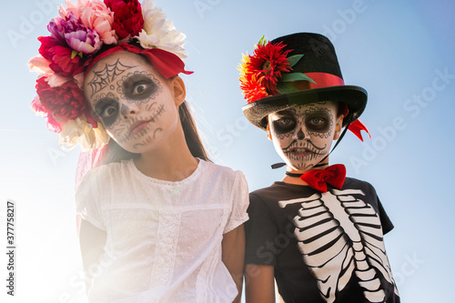 Gloomy and scary halloween boy and girl with painted faces looking at you #377758217