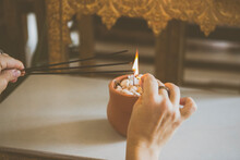 Buddhist Temple At Santa Teresa, Rio De Janeiro, Brazil. Hand Lighting Up Incense On A Candle Inside A Small Pottery Vase.