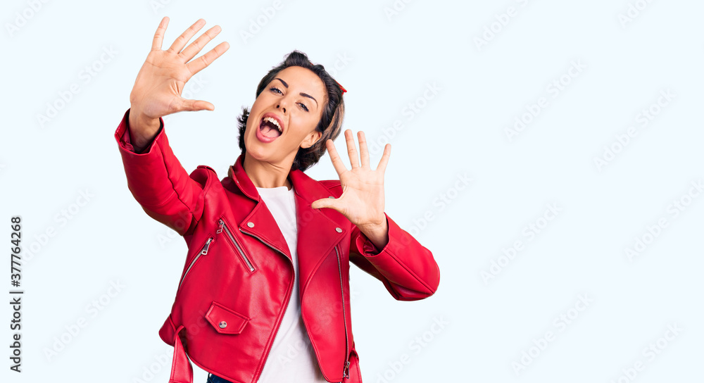 Fototapeta Young beautiful woman wearing red leather jacket showing and pointing up with fingers number ten while smiling confident and happy.
