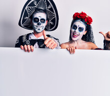 Young Couple Wearing Mexican Day Of The Dead Costume Holding Blank Empty Banner Approving Doing Positive Gesture With Hand, Thumbs Up Smiling And Happy For Success. Winner Gesture.